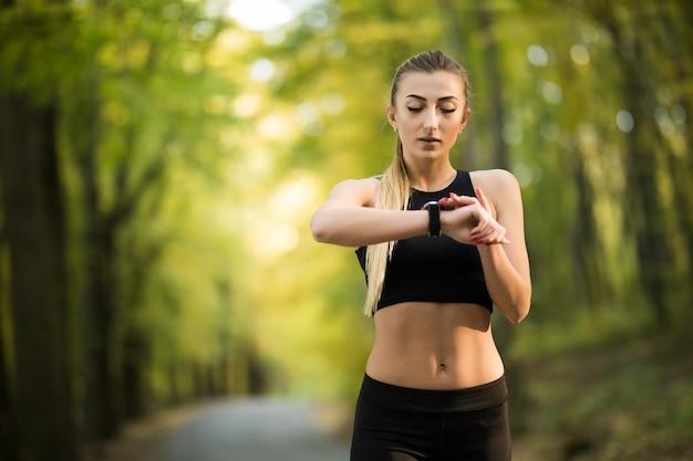 Atleta joven atractiva practicando fitness al aire libre y configurando su monitor de cardio smartwatch antes de correr en el parque