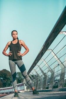 Atleta joven confiado en ropa deportiva de pie en el puente con las manos en las caderas