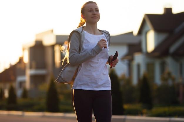 Atleta joven corredor femenino durante el jogging en las calles de la ciudad bajo el sol