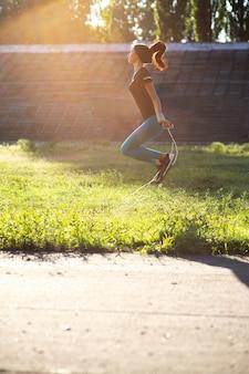 Atleta joven en ropa deportiva haciendo ejercicio con saltar la cuerda al atardecer