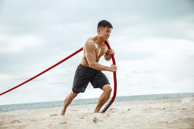 Atleta joven sano haciendo sentadillas en la playa