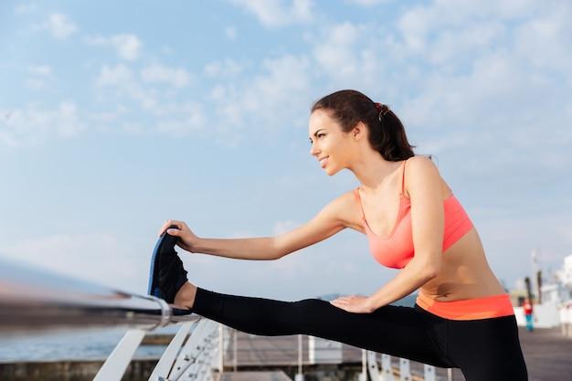 Atleta joven sonriente haciendo ejercicios de estiramiento en el muelle por la mañana