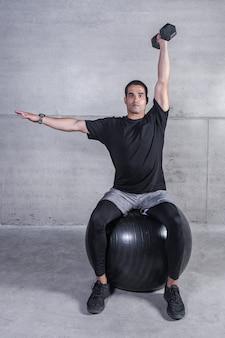 Atleta con mancuernas sentado en la pelota medicinal