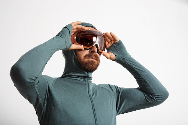Atleta masculino barbudo en suite térmica de capa base usa gafas de snowboard