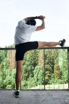 Atleta masculino concentrado corriendo escaleras arriba para hacer el entrenamiento más intensivo. deportivo apuesto joven entrenando solo al aire libre. concepto de entrenamiento de escalera.