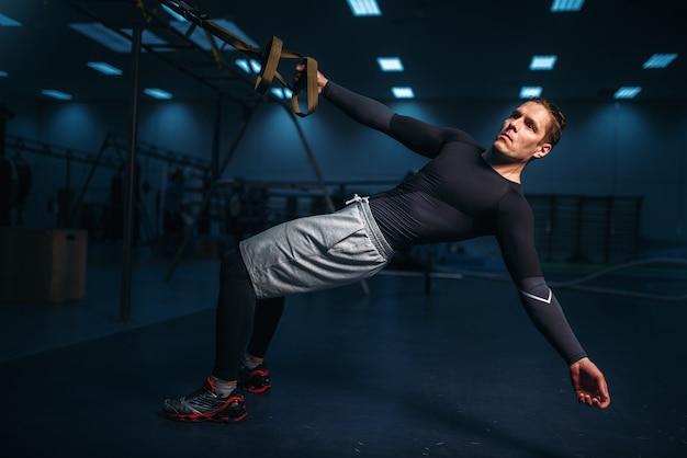 Atleta masculino en entrenamiento, entrenamiento de estiramiento con cuerdas en el gimnasio.