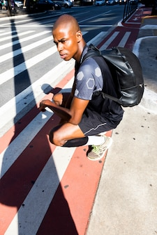 Un atleta masculino joven africano que se agacha en el borde de la carretera que mira lejos