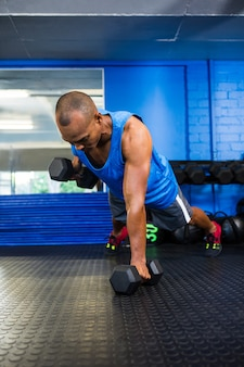 Atleta masculino levantando pesas en el gimnasio