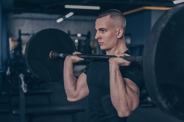 Atleta masculino musculoso trabajando con barra en el gimnasio studio