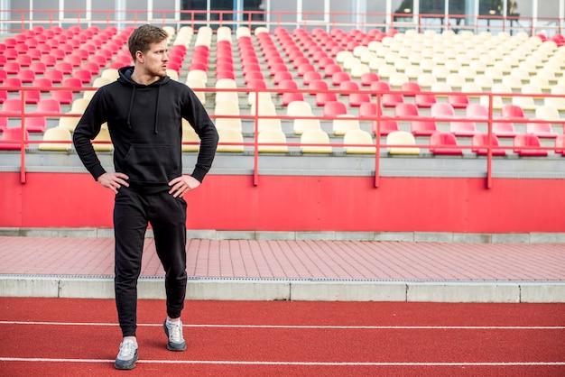 Un atleta masculino de pie delante de la grada haciendo ejercicio