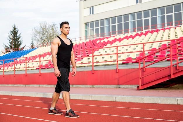Un atleta masculino de pie delante de la grada en la pista de carreras
