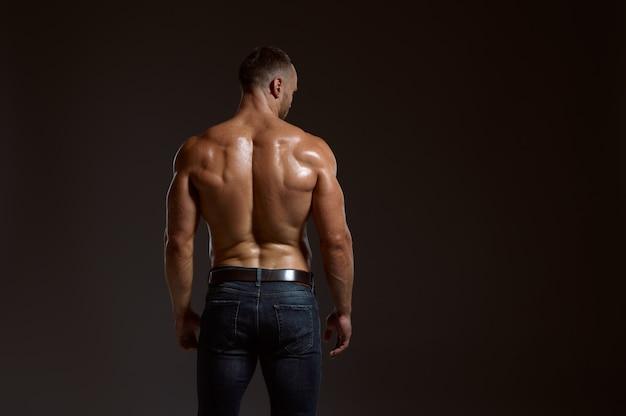 Atleta masculino con poses de cuerpo musculoso en estudio