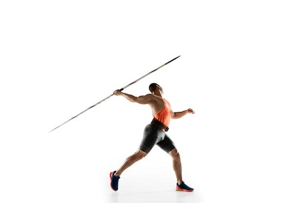 Atleta masculino practicando lanzamiento de jabalina en estudio blanco.