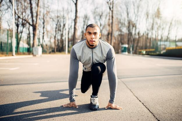 Atleta masculino se prepara para correr en el parque de otoño