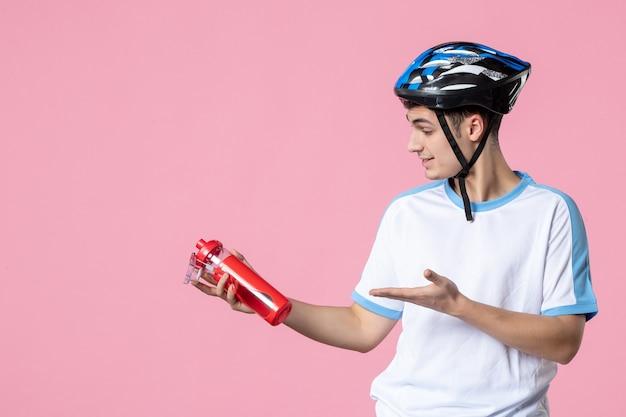 Atleta masculino de vista frontal en ropa deportiva con casco y botella de agua