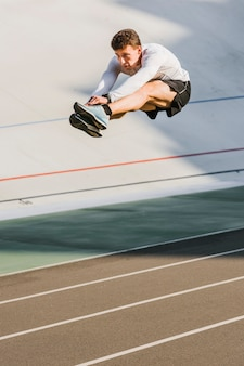 Atleta en medio de un salto de longitud.