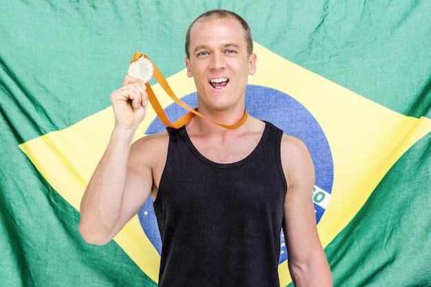 Atleta mostrando su medalla de oro frente a la bandera brasileña