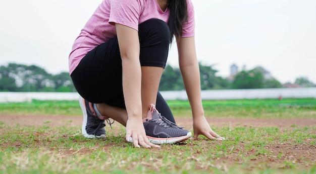 Atleta mujer asiática preparándose para comenzar a correr en pista