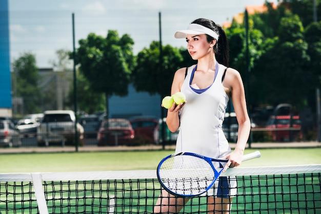 Atleta mujer en ropa deportiva con raqueta y pelotas