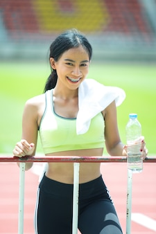 Atleta mujer toma un descanso y bebe agua