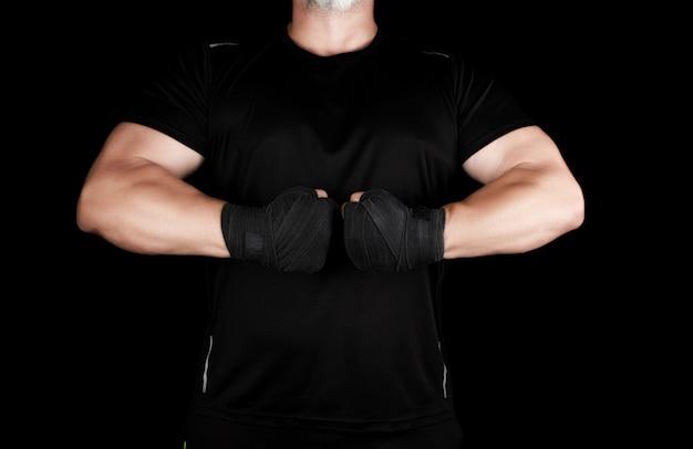 Atleta musculoso adulto en ropa negra con manos rebobinadas con una venda negra