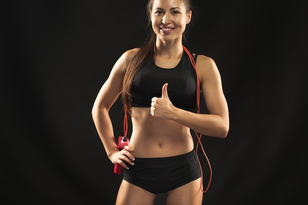 Atleta musculoso joven con una comba en negro