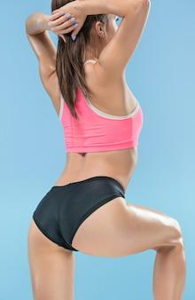 Atleta musculoso joven posando en el estudio en azul