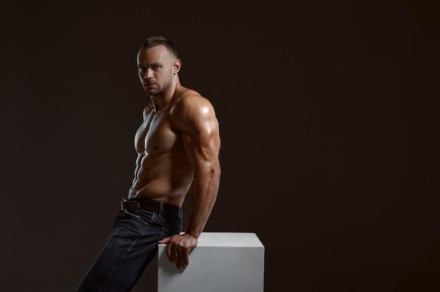 Atleta musculoso masculino sentado en el cubo en estudio, fondo oscuro. un hombre con complexión atlética, deportista sin camisa en pantalones vaqueros, estilo de vida activo y saludable