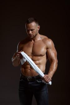 Atleta musculoso masculino sostiene su camisa en las manos en estudio, fondo oscuro. un hombre con complexión atlética, deportista sin camisa en pantalones vaqueros, estilo de vida activo y saludable