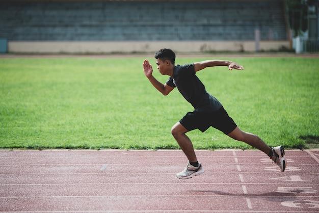 Atleta de pie en una pista de atletismo para todo clima