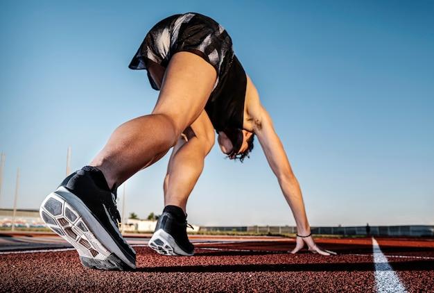 Atleta en pista de atletismo listo para correr