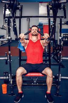 El atleta poderoso que hace ejercicios en los músculos pectorales.