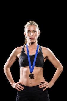 Atleta posando con medalla de oro alrededor del cuello.