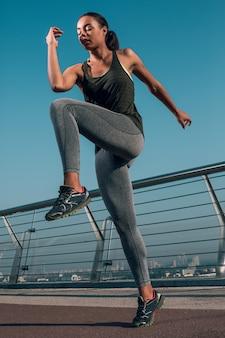 Atleta profesional al aire libre poniendo la rodilla al codo mientras se calienta