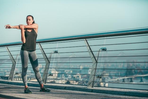 Atleta profesional concentrado de pie en el puente y tirando de su brazo