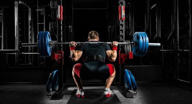 El atleta profesional se sienta con una barra sobre sus hombros y se prepara para pararse con ella.
