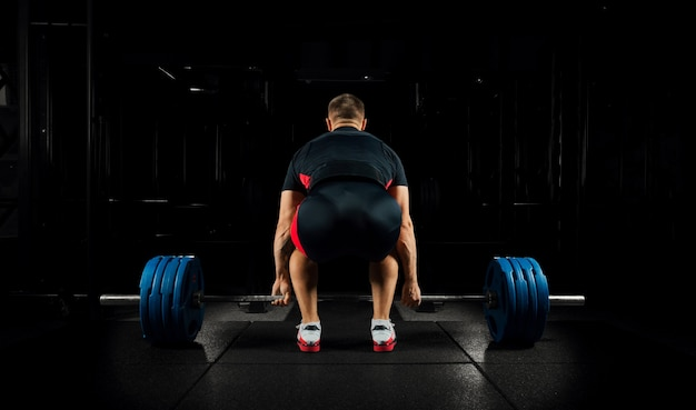 El atleta profesional se sienta frente a la barra y se prepara para levantarla.