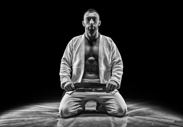 Atleta profesional se sienta en el gimnasio. concepto de karate, jiu-jitsu, sambo, judo. técnica mixta