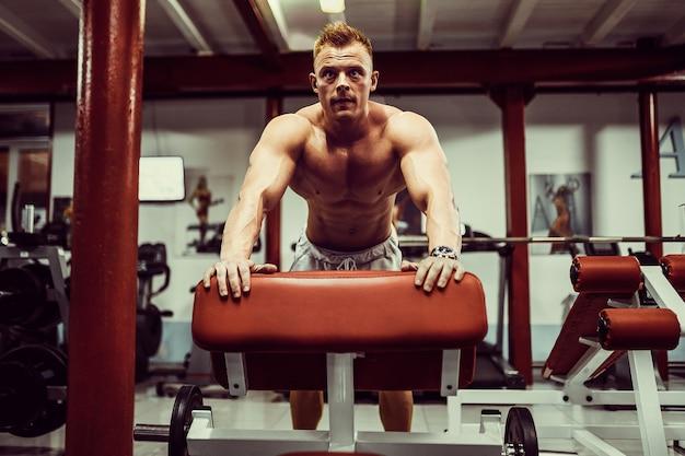 Atleta saludable haciendo flexiones como parte del entrenamiento de culturismo en el banco
