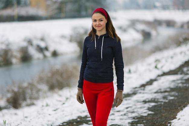 Atleta de sexo femenino joven sonriente que se coloca en invierno