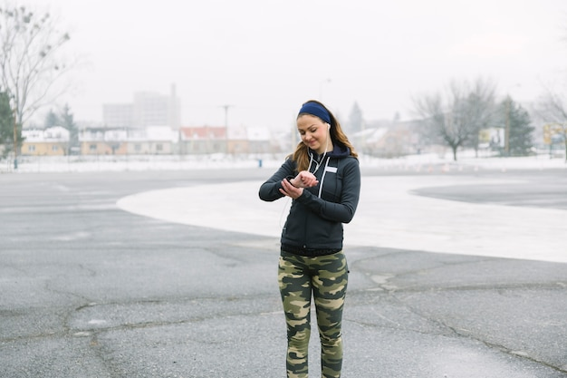 Atleta de sexo femenino que mira tiempo mientras que ejercita en la calle