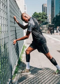 Atleta de sexo masculino joven africano que ejercita en al aire libre en ciudad