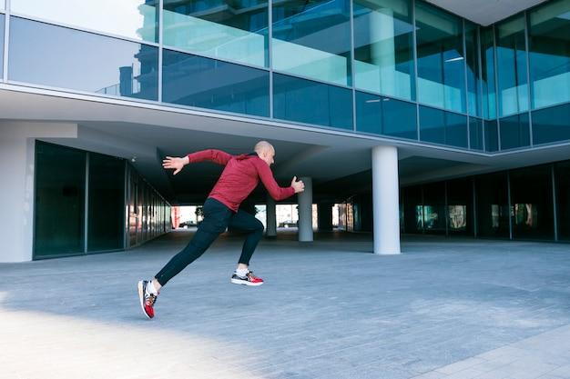 Atleta de sexo masculino joven sano juguetón que corre cerca del edificio corporativo