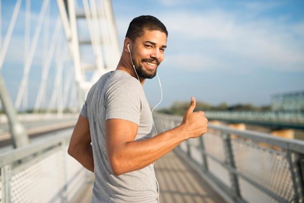 Atleta sonriente con auriculares sosteniendo thumbs up listo para entrenar