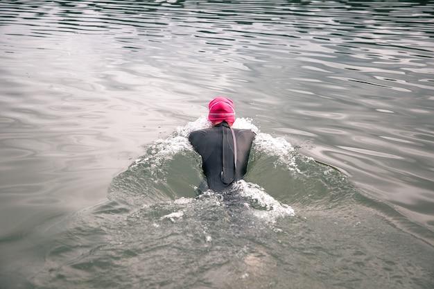 El atleta se sumerge en el agua con un traje de neopreno.
