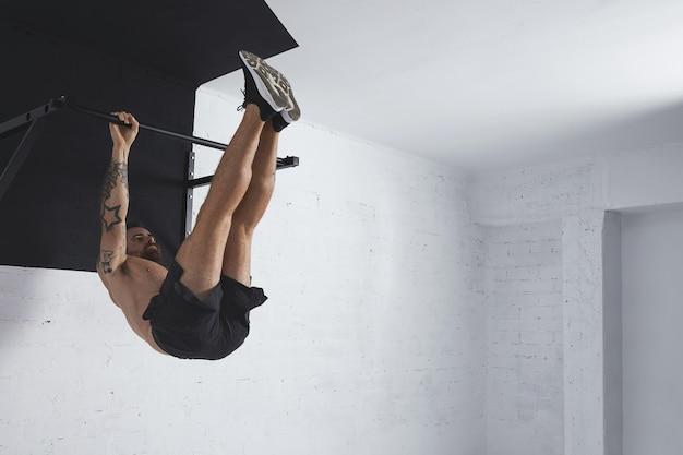 Atleta tatuado fuerte muestra cómo hacer movimientos de calistenia paso a paso la pierna completa se levanta en la barra de tiro