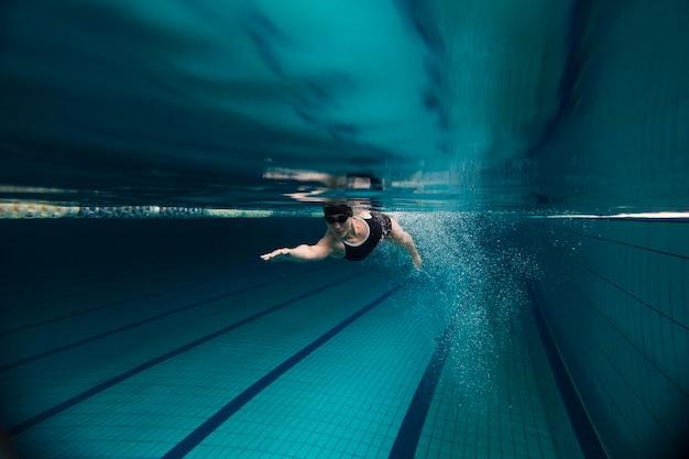 Atleta de tiro completo bajo el agua