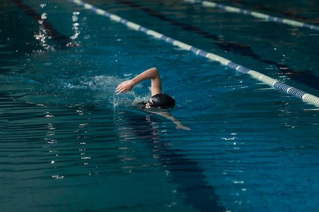 Atleta de tiro completo nadando en la piscina