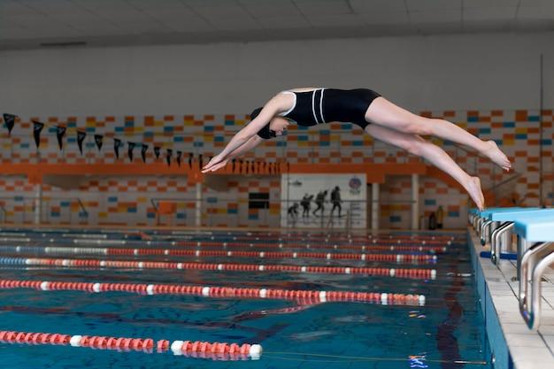Atleta de tiro completo saltando en la piscina