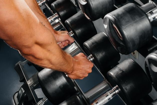 Un atleta toma pesas de bastidores en el gimnasio, primer plano. fitness, culturismo